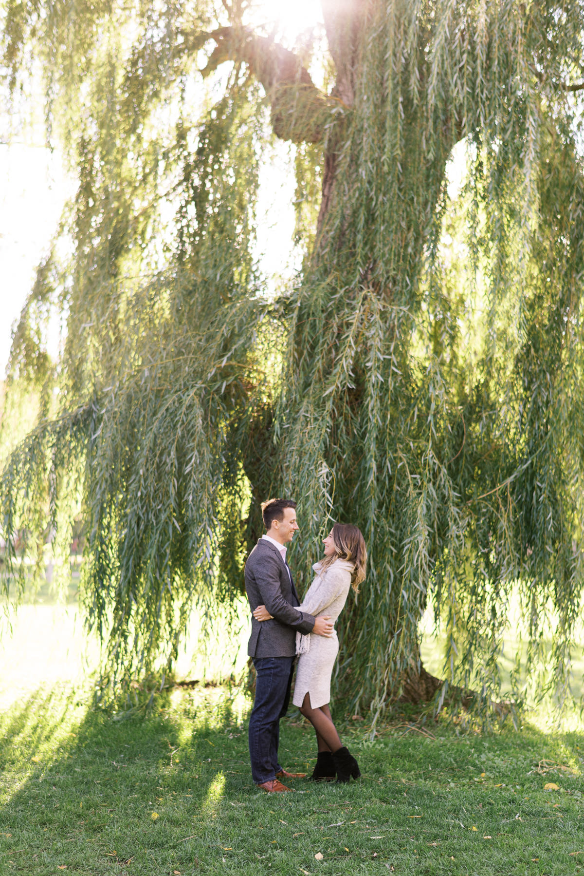 Portrait of a couple standing under a willow tree