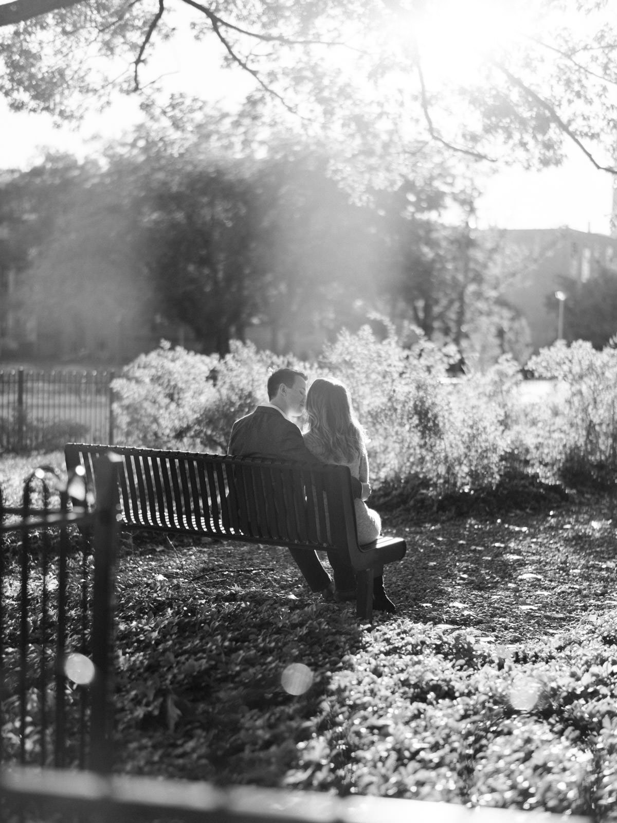 kissing on a bench in the fall