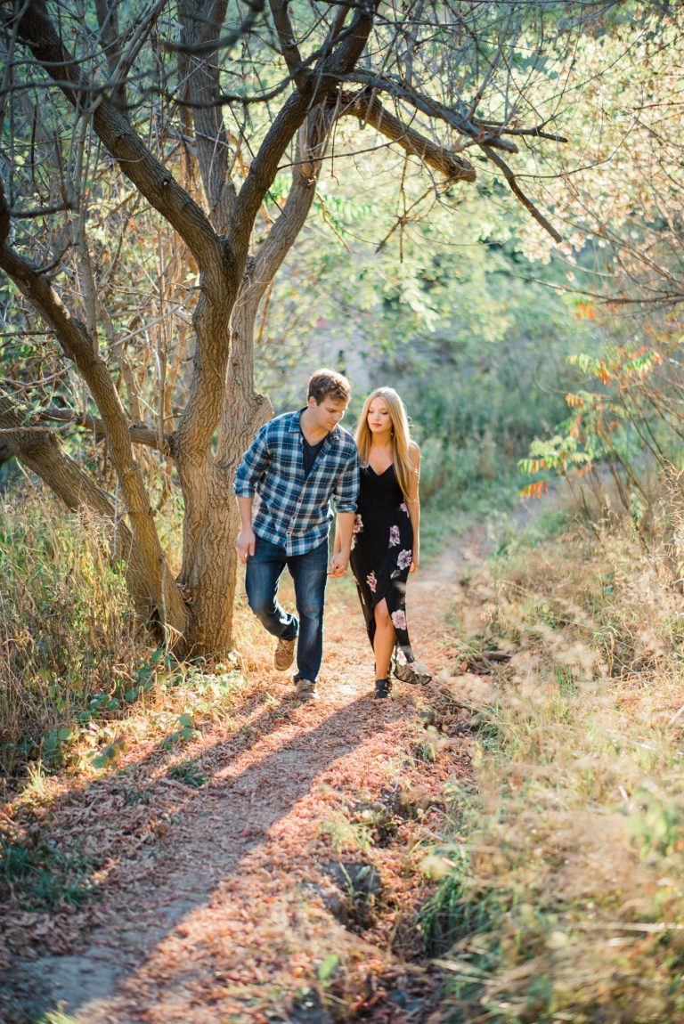 Couple walking through a forest trail at sunset