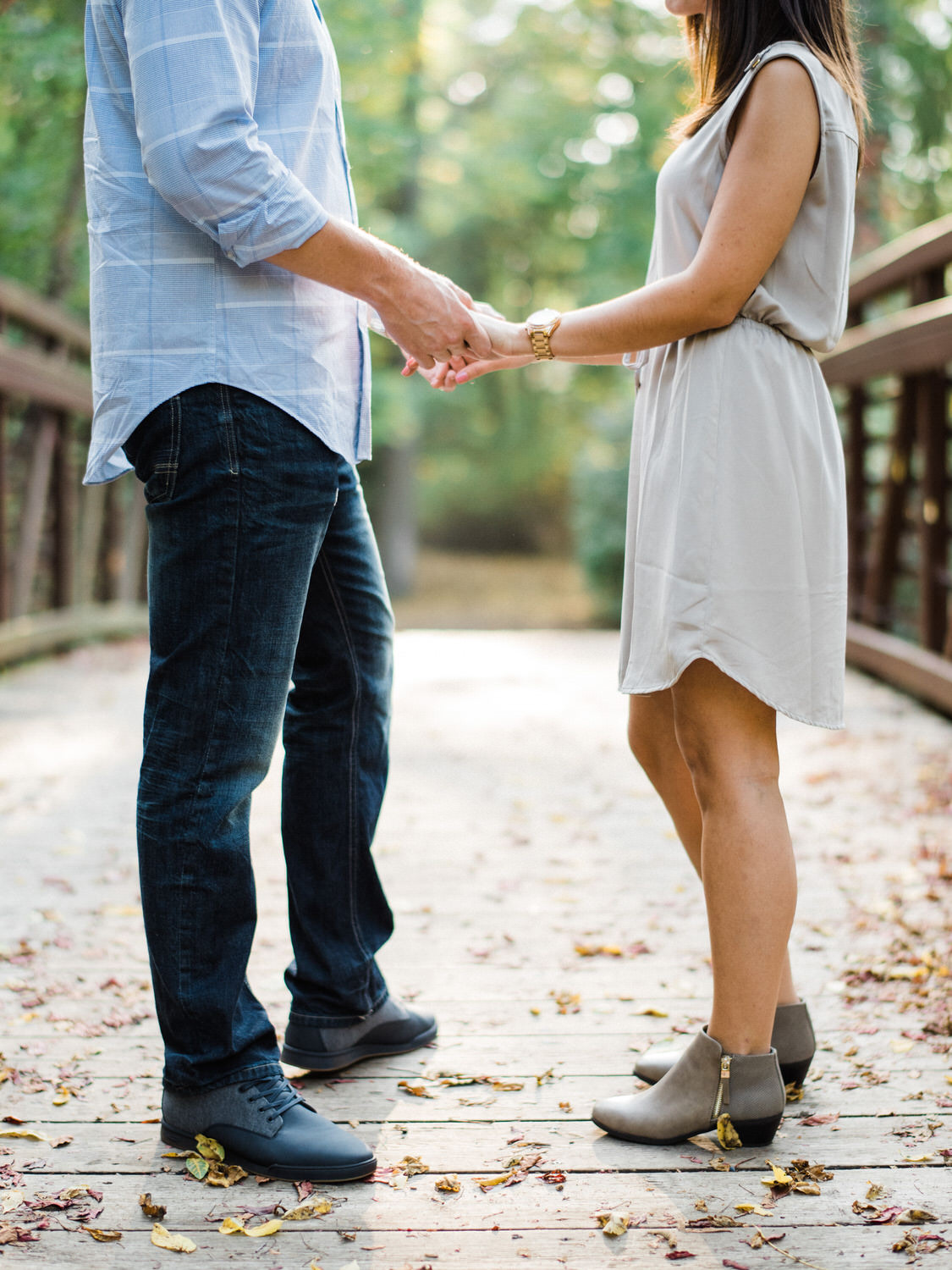 Holding hands on a bridge, close cropped