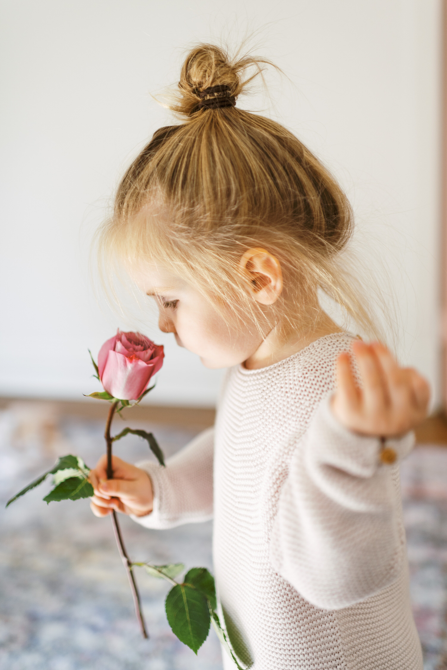 daughter smelling pink flower