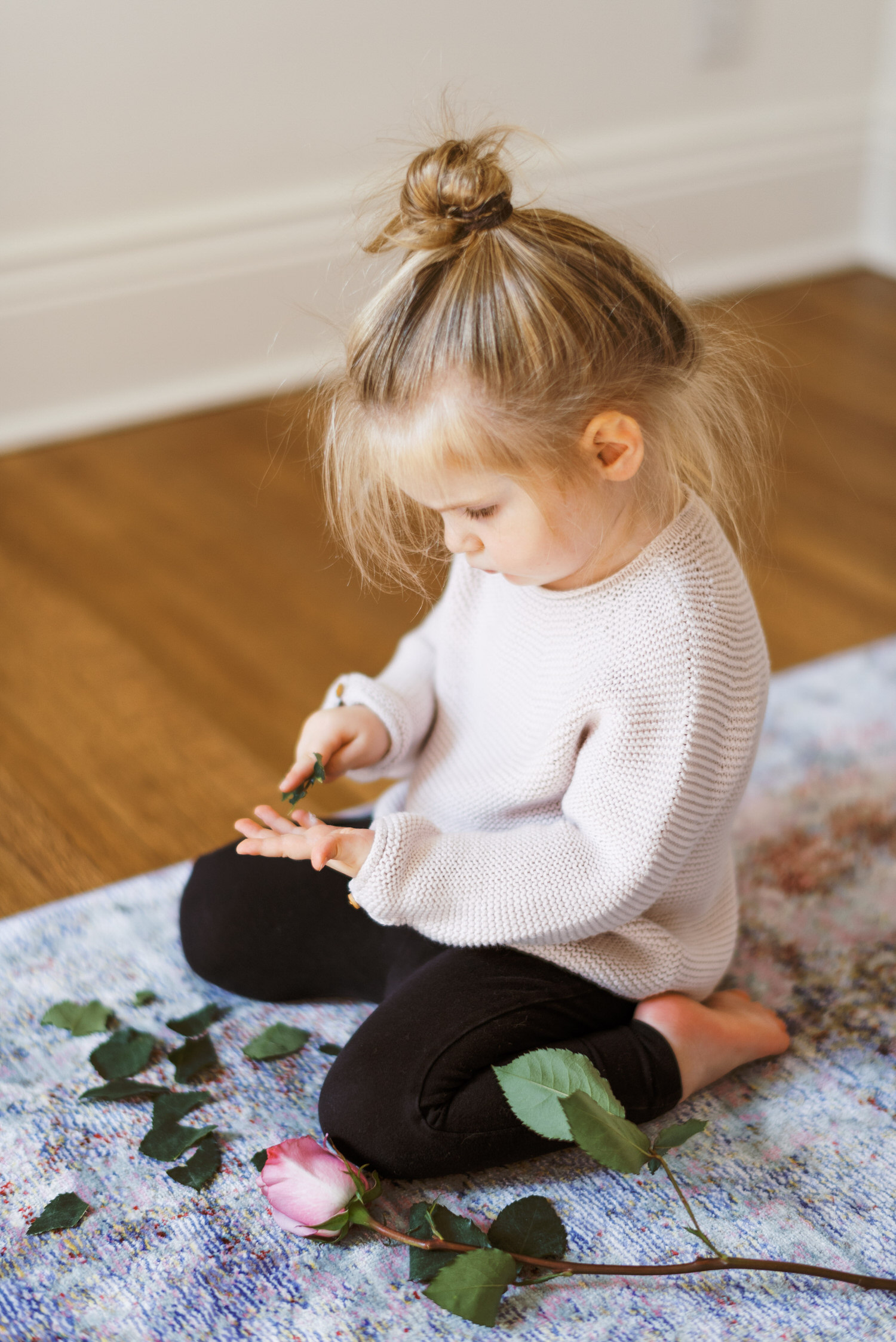 toddler playing with flower leaves during portrait session