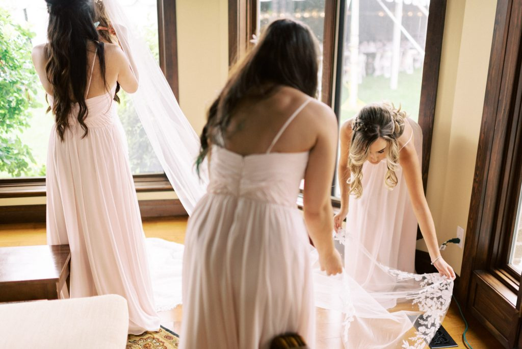 bridesmaids helping with the dress and veil