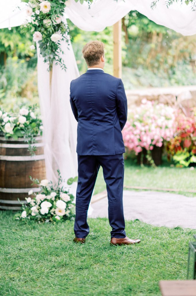 groom standing awaiting his first look