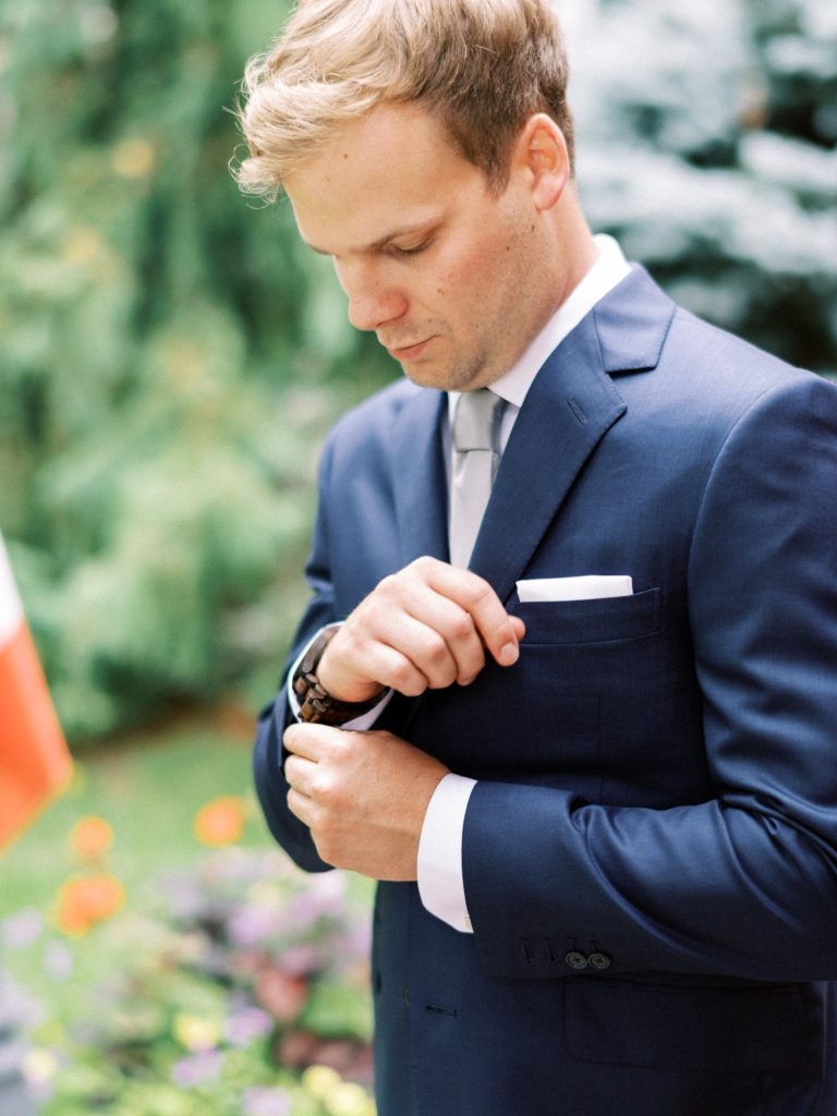 groom fixing up his watch and cuffs