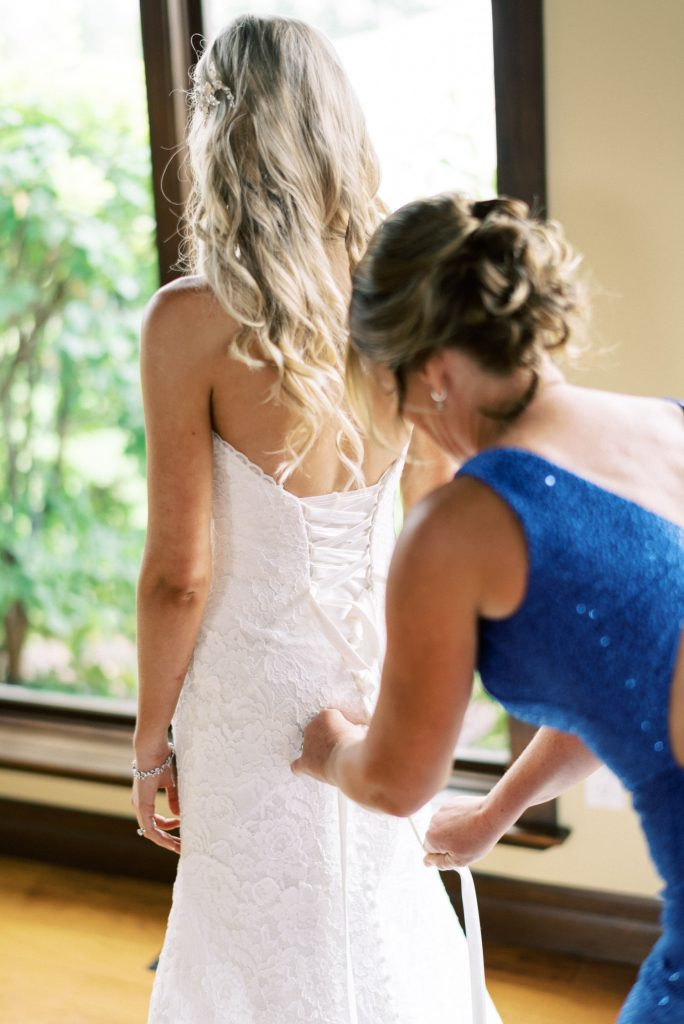 mother of the bride helping her do up her dress