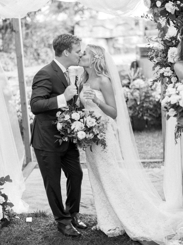 bride and groom kissing again with champagne glasses