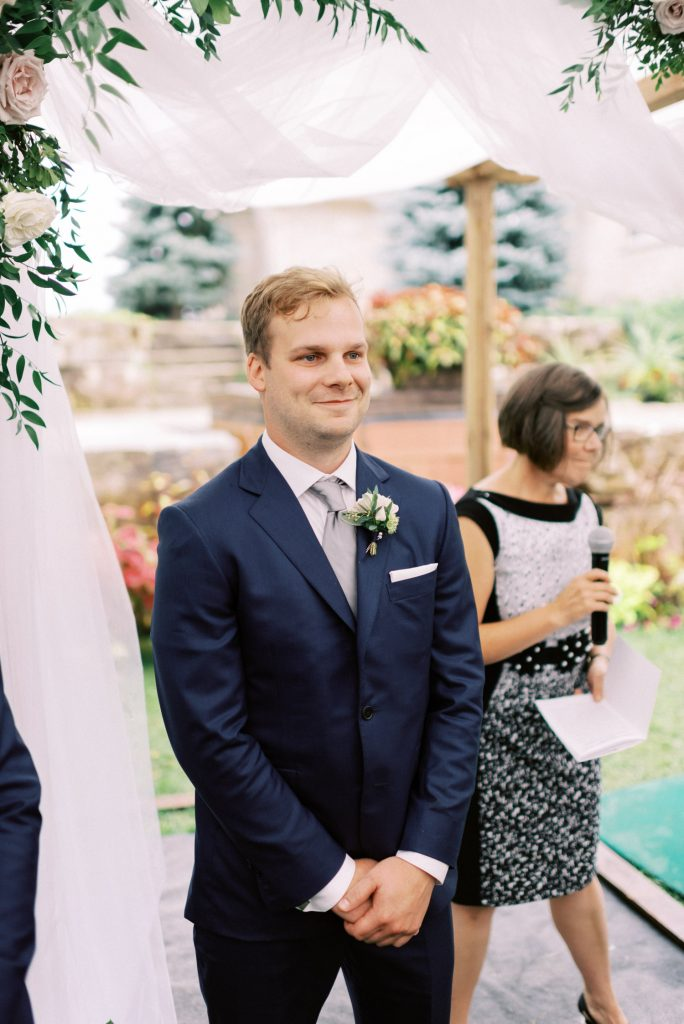 groom smiling, waiting for the bride