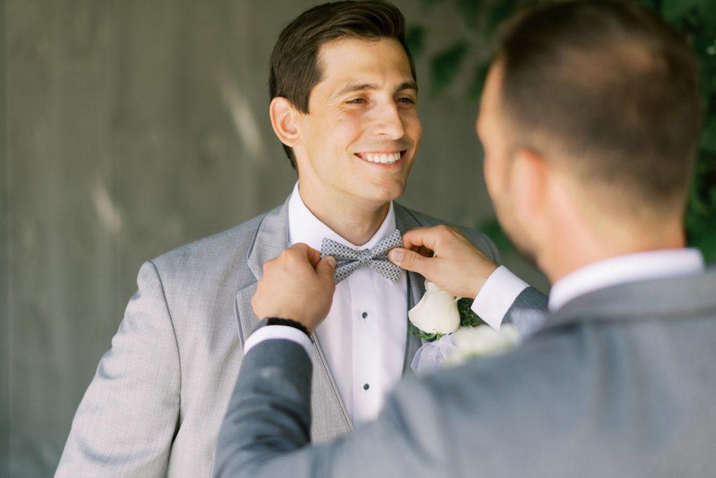 groomsman fixing grooms bowtie
