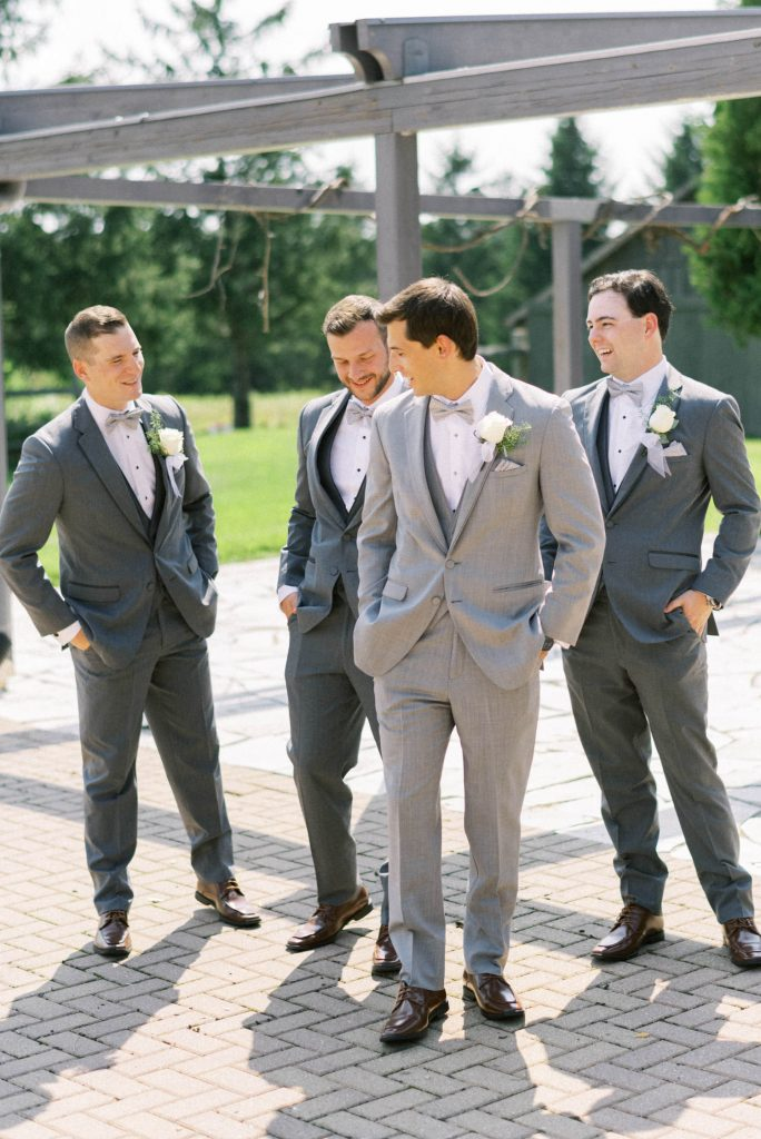 casual groomsmen portrait behind bellamere
