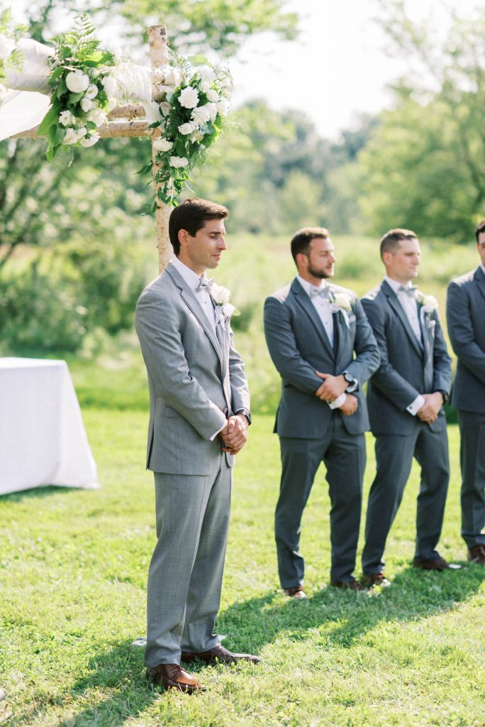 groom holding back tears, watching bride come down the aisle