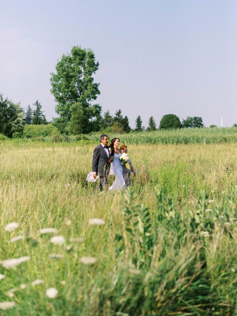 bride walking through the tall grass at bellamere toward the ceremony