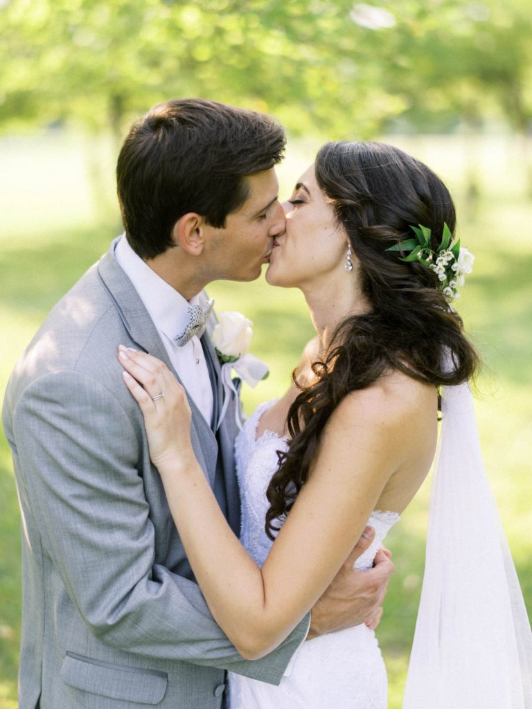 bride and groom kissing in the orchard at bellamere