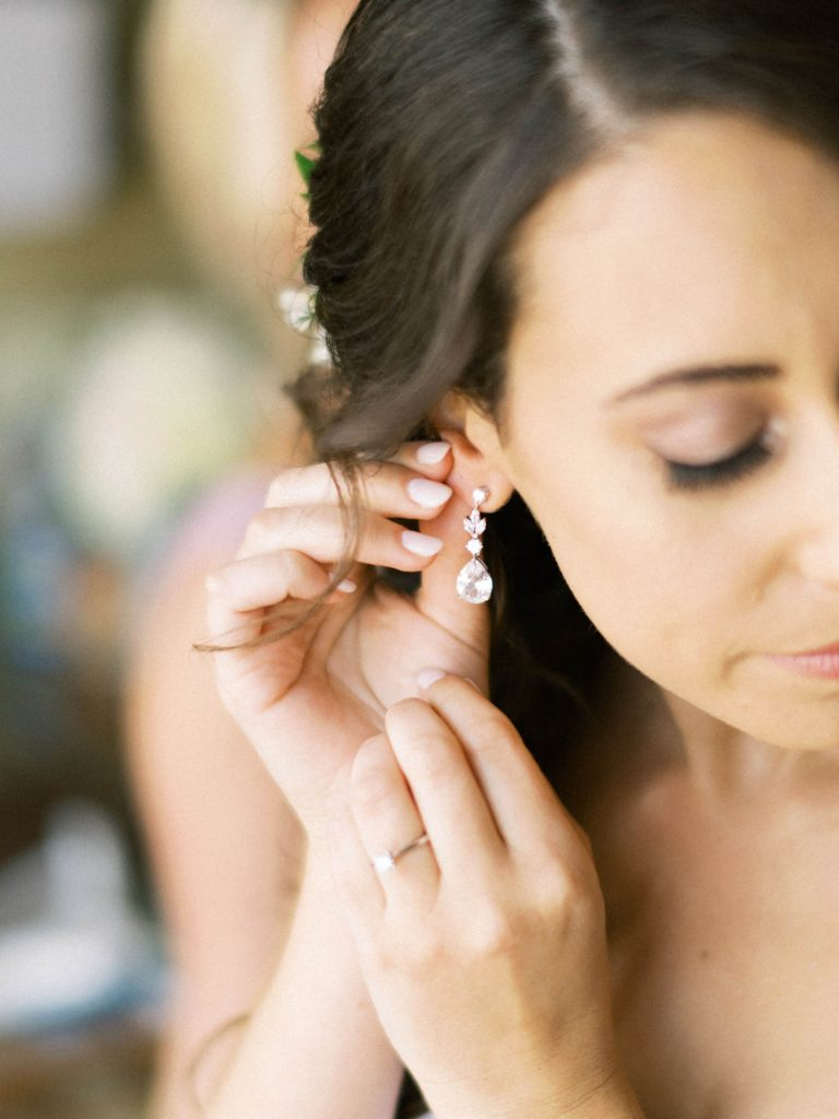 bride putting her earrings on