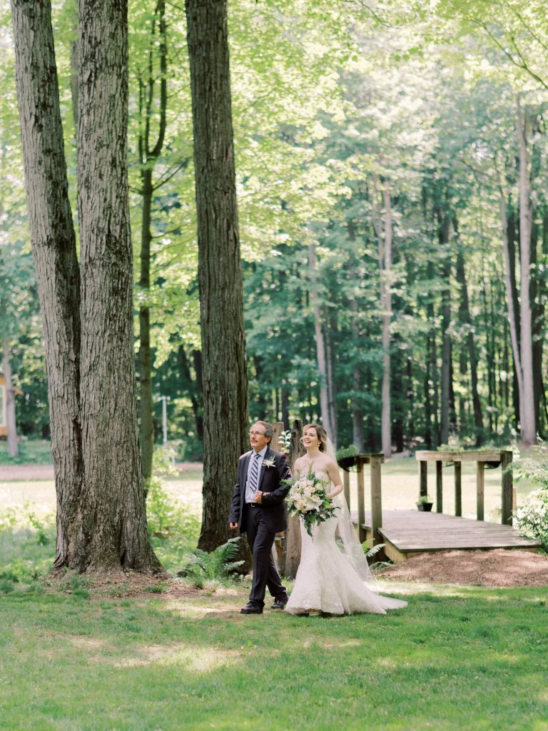 bride walking down the forest aisle with father