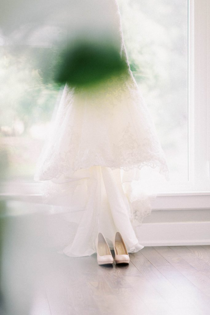 obscured view of wedding dress in window, with shoes